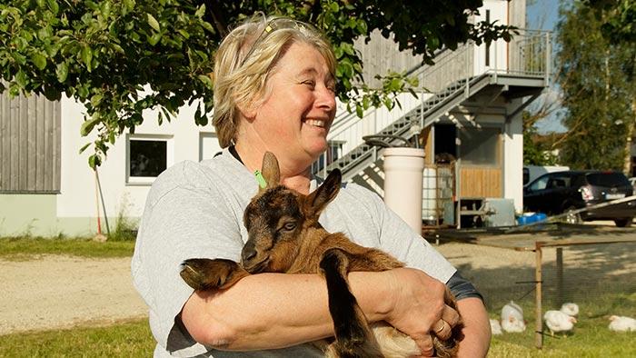 Anita Liebert mit einem Ziegenkitz im Arm.