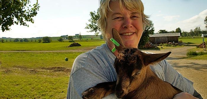 Martina hält ein Kitz in der Hand. Im Hintergrund sind grüne Wiesen zu sehen.