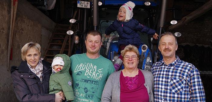 Junioren und Senioren stehen vor einem Traktor.
