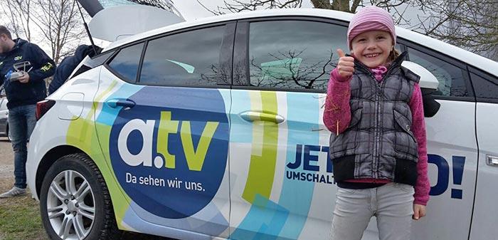 Katharina steht vor dem a.tv-Auto und zeigt Thumbs up.